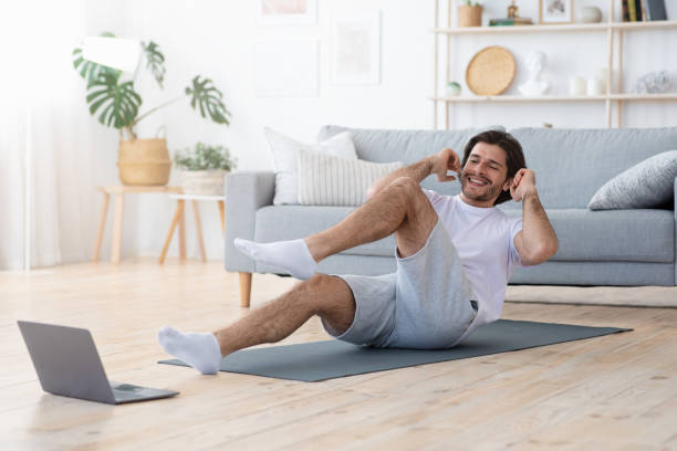 Positive guy making exercises at home, looking at laptop screen